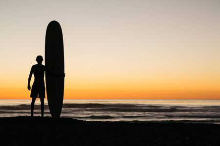 over the edge: Surfer and his board enjoying a post surf evening glow