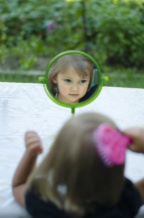 in vain: Girl brushing her hair looking in  mirror
