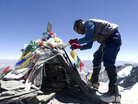 Man putting prayer flags on summit of Kangaytse in Himalayas, Ladakh, India
