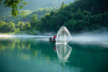 net: Man in boat throwing fishing net, Chenzhou, Hunan, China LANG_EVOIMAGES