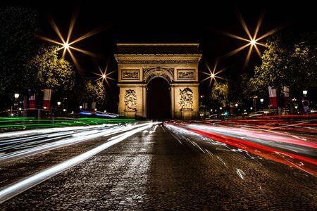 Traffic light trails by Arc de Triomphe at night, Paris, France