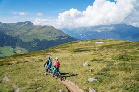 Two women mountain biking in swiss alps, Davos, Graubunden, Switzerland