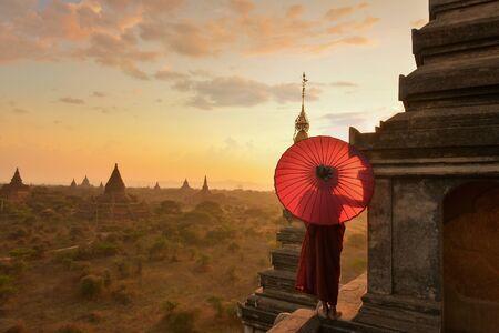 monastic: Novice Monk standing on temple at sunset, Bagan Myanmar LANG_EVOIMAGES
