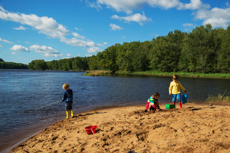 Three children fishing and playing on beach LANG_EVOIMAGES