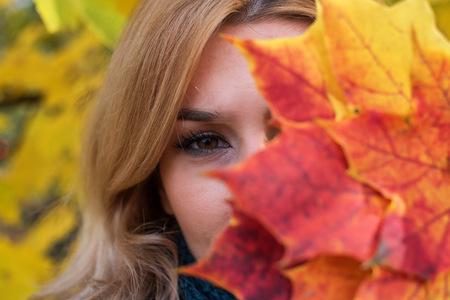 Woman hiding behind an autumn leaf