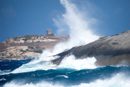 Waves hitting rocks along coastline, Corsica, France