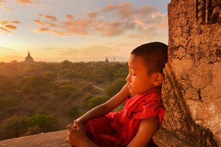 only boys: Novice monk sitting on temple at sunset, Bagan, Myanmar
