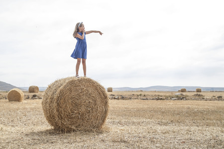 Girl standing on a hay bale in a field LANG_EVOIMAGES
