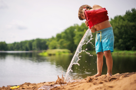 Boy emptying a bucket of water on the beach