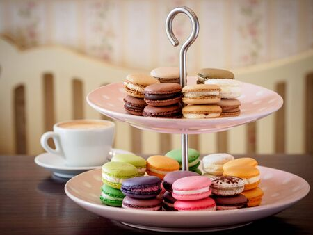 Macaroon selection on cake stand with cappuccino