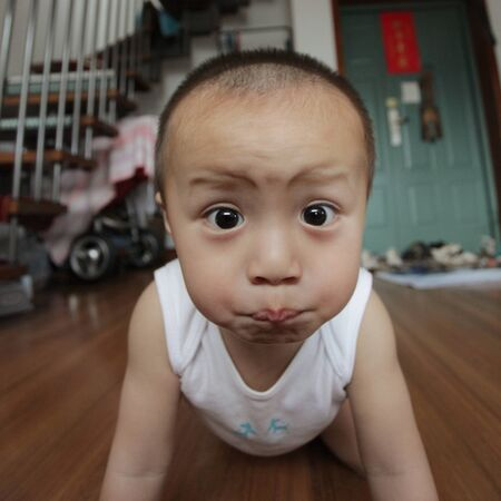 Boy crawling on floor making a funny face LANG_EVOIMAGES