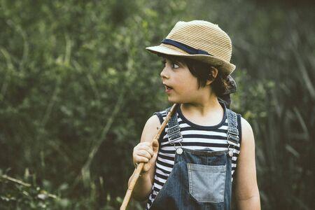 Boy walking through field carrying a stick