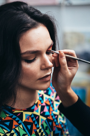 make up artist applying eye shadow to a woman
