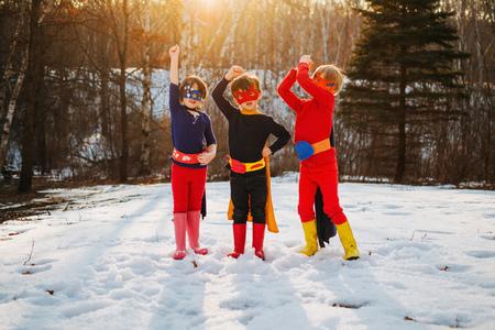 niños vistiendose: Three children standing on frozen lake wearing superhero costumes LANG_EVOIMAGES