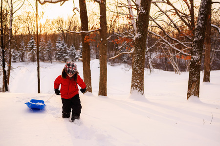 Boy pulling sledge up a hill at sunset