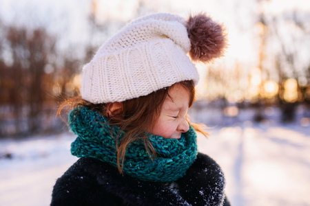 Girl in bobble hat and scarf standing in snow pulling a funny face