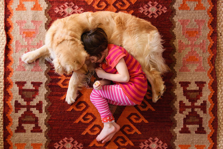 Overhead view of girl lying on floor with a golden retriever dog LANG_EVOIMAGES