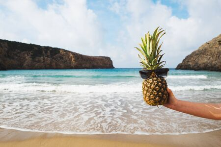 Womans hand holding a pineapple wearing sunglasses LANG_EVOIMAGES