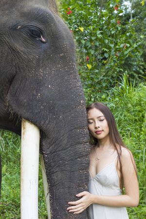 Woman leaning against elephant with her eyes closed, Tegallalang, Bali, Indonesia