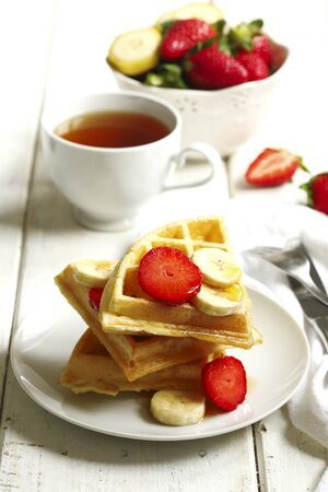 Tea and Belgian waffles with strawberries, banana and maple syrup