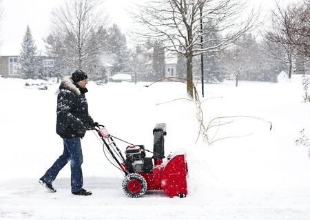 Man using a snow blowing machine, Canada LANG_EVOIMAGES