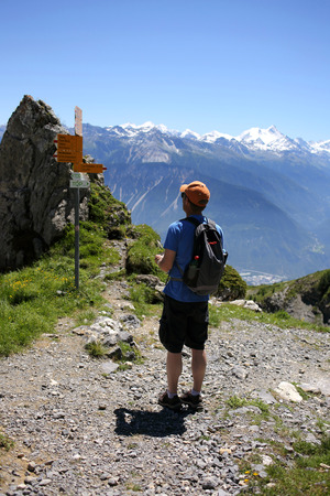 one mature man only: Hiker standing on footpath in mountains, Switzerland