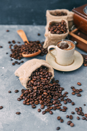 Coffee grinder with sacks of coffee beans and a cup of coffee