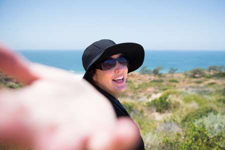 personal perspective: Woman on the beach with her arm outstretched to follow her