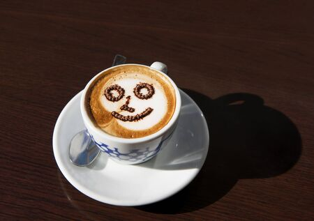 Cup of coffee with smiley face LANG_EVOIMAGES