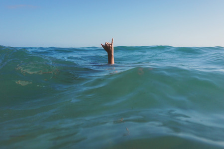 Teenage girls hand coming out of the ocean making a Hang Loose sign LANG_EVOIMAGES
