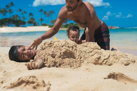 Father and daughter burying son in sand on the beach LANG_EVOIMAGES