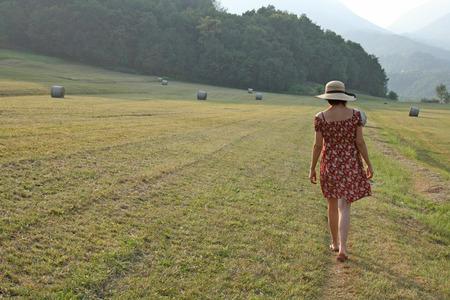 Woman walking in a field amongst hay bales
