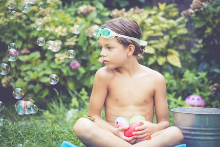 Boy sitting in the garden looking at soap bubbles floating mid air
