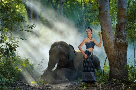 Woman in traditional Thai clothing standing in forest with an elephant, Thailand LANG_EVOIMAGES