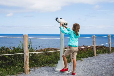 Boy looking through binoculars by the ocean