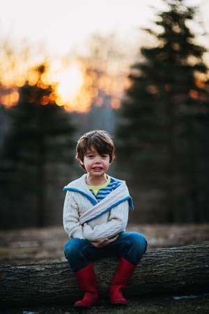 Boy sitting on a log laughing