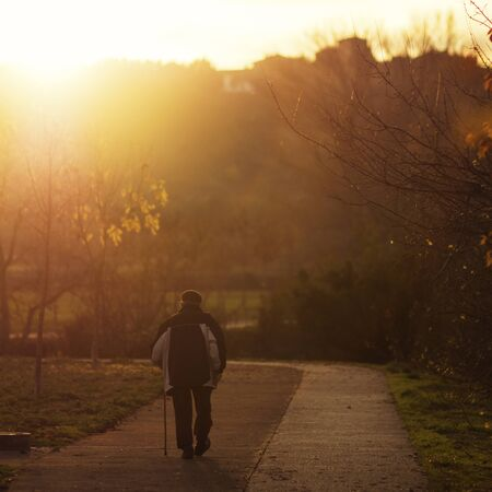 Senior man walking down footpath at sunset