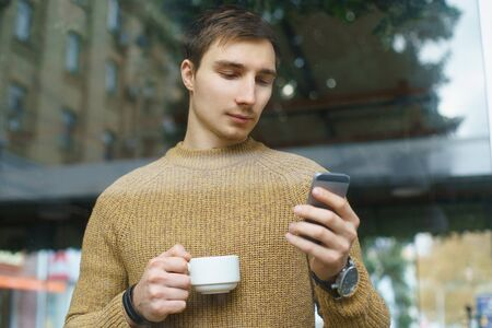 man with a cup of coffee standing by a window looking at his mobile phone