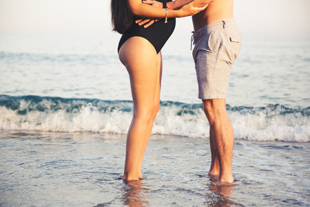 Pregnant couple standing on beach LANG_EVOIMAGES