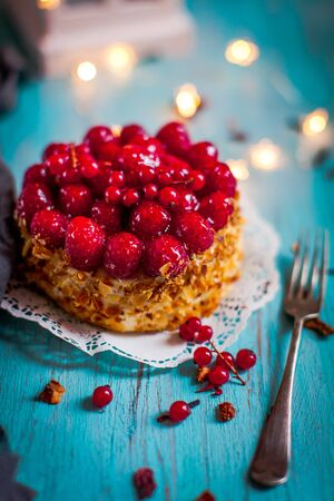 Sponge cake on a table with fresh raspberries and redcurrants