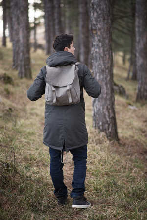 Man standing in forest carrying a backpack