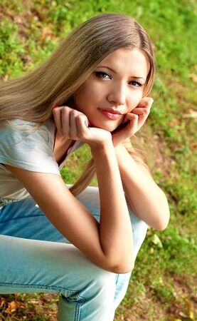 Young beautiful blond girl sitting on the grass  Stock Photo - 7795267