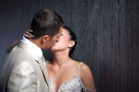 Bride and groom is kissing in the dark room photo