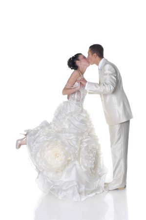 Isolated on white kissing bride in wedding dress and groom photo