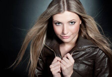 Beautiful blond girl on the black background with blowing hair  photo