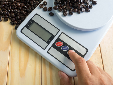 hand press: hand press on  digital measuring device and coffee beans Stock Photo