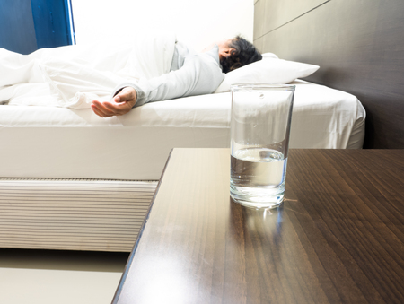 grandmom sleeping in weakness concept, focus on glass Stock Photo