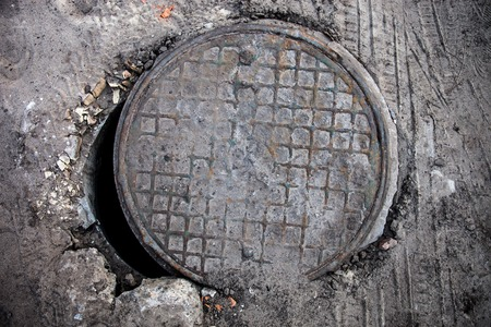 confined space: Open old manhole with metal cover