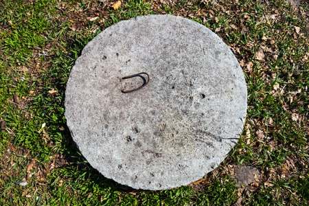 confined space: Concrete manhole cover in the grass in the sunny day