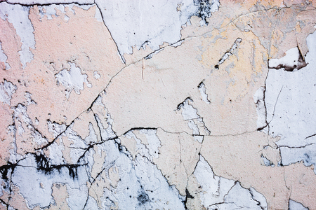 Cracked concrete surface with the remains of sandy-tan paint photo